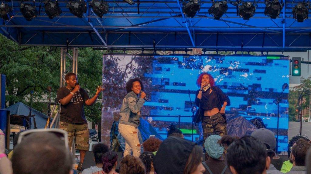 three performers rapping on the AS220 Foo Fest stage to a large crowd. Photo by Elie Lebron