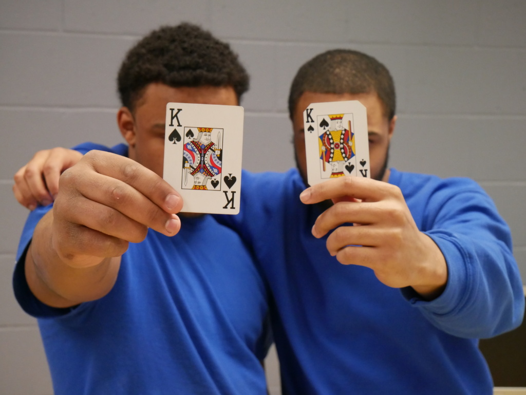 photo of two young men in blue shirts, arms on each other's shoulders. They're each holding a king from a deck of cards in front of their faces.