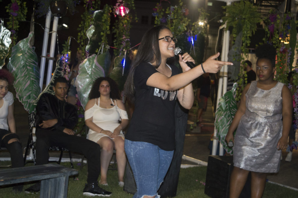 FW4 performance. performer jayden cabral rapping on the indigo garden set, while other cast members watch seated in the background. photo by Diana Izaguirre