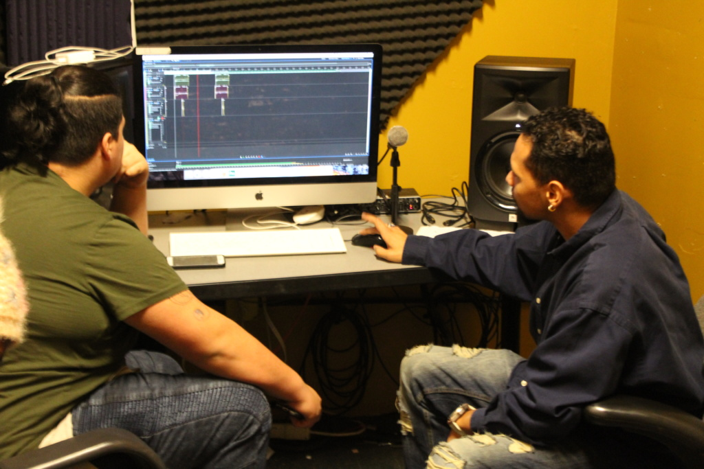 Instructor Chris helps an NLA student with the recording software in the Delgado Studio
