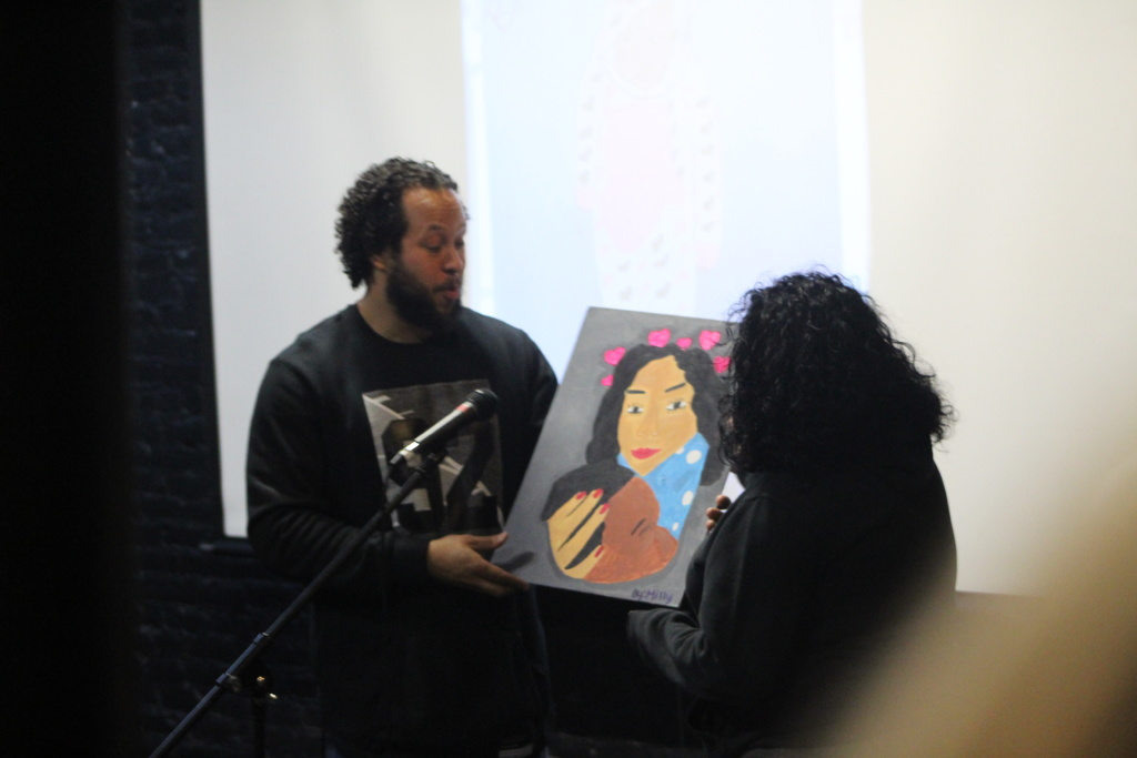 NLA staff Chachi shows off an NLA student painting
