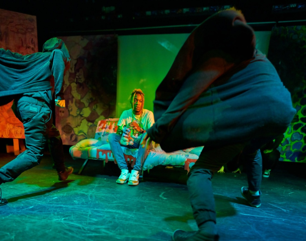 FW5 performance. Dancers in black hoods rush toward center stage where Marley is seated. Photo by James Lastowski