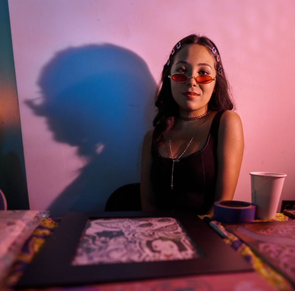 youth artist Ronnie sits at her table displaying her drawings for sale at FW5. Photo by James Lastowski